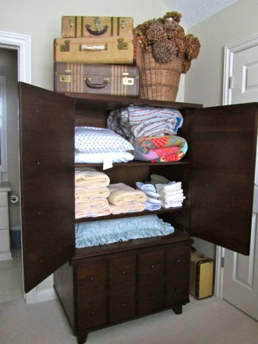 An old TV armoire now houses extra blankets, pillows and towels for guests.
