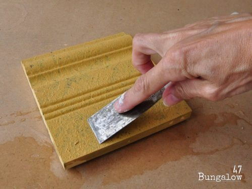 Step 4: Holding the trowel flat, drag it back along the moistened paint to flatten the stipple bumps